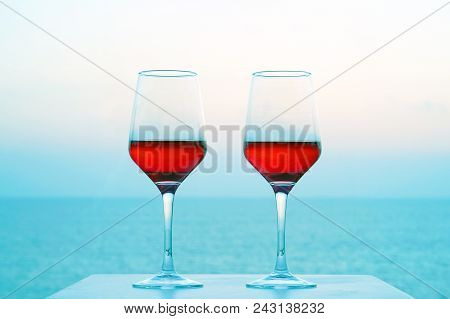 Two Glasses Of Red Wine On A Background Of Sea Horizon Morning. Two Glasses Of Red Wine With Blue Se