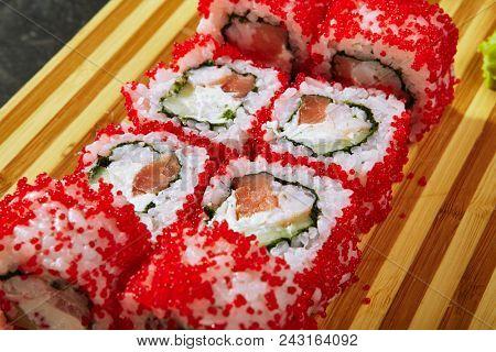 Asian menu. Sushi Roll with Masago caviar outside. Salmon, shrimp and cucumber inside
