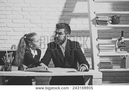 Back To School. Happy Kid Having Fun. Teacher And Schoolgirl In Study Room On White Brick Background