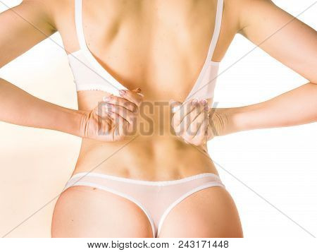 Close-up On Woman Back With A Hand Try To Take Her Bra Off By Unhooking The Clasp Of Her Bra.