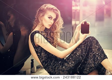 Woman Face Beauty. Girl With Perfume, Young Beautiful Woman Holding Bottle Of Perfume And Smelling A