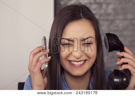 Laughing Businesswoman Conducts Conversations Over Two Phones