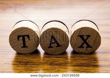 Tax Word On Wooden Wheels. Tax And Legal Concept On The Wooden Background. Business Concept With Wor