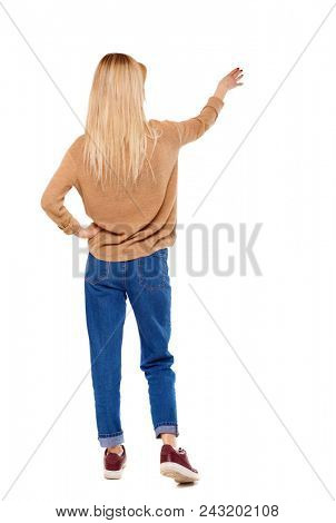 Back view of a woman in a sweater points his hand upwards. Rear view people collection.  backside view of person.  Isolated over white background. Female student in jeans shows her hand up