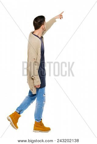 Side view of a man walking with a pointing hand. going  guy showing.  backside view of person.  Rear view people collection. Isolated over white background. The guy in the shoes shows on the sights