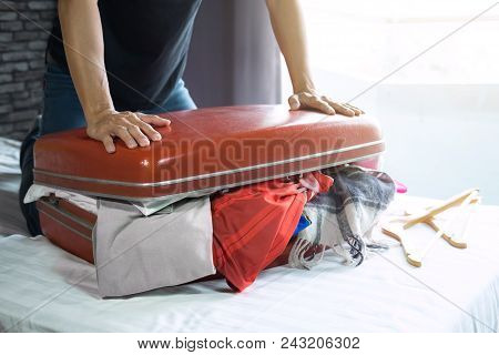 Travel And Vacation Concept, Happiness Young Man Packing A Lot Of His Clothes And Stuff Into Suitcas
