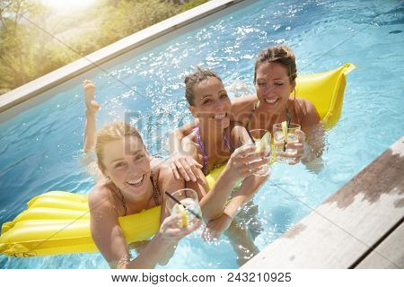 Girls in swimming-pool drinking cocktails