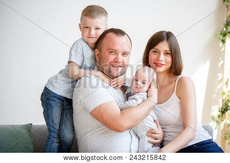 Portrait of couple with two young sons sitting on sofa in apartment