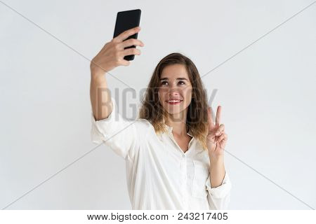 Smiling Young Woman Taking Selfie Photo And Showing Victory Sign. Selfie Photo Concept. Isolated Fro