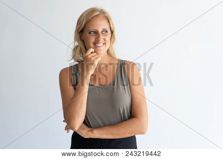 Portrait Of Mid Adult Blond-haired Woman Standing And Smiling. Pretty Caucasian Lady Wearing Grey Ta