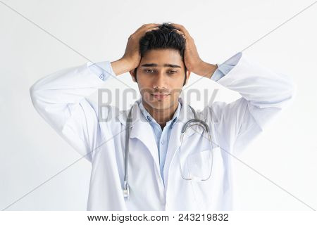 Portrait Of Young Indian Medical Student Holding Head In Stress. Frustrated Doctor Wearing Medical G