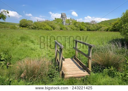 Corfe Castle And The Medieval Village Viewed From The Countryside With A Little Wooden Footbridge In