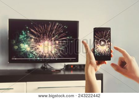 Man With Smartphone Connected To A Tv Watching Video At Home. Transfer Video From Phone To Tv Screen