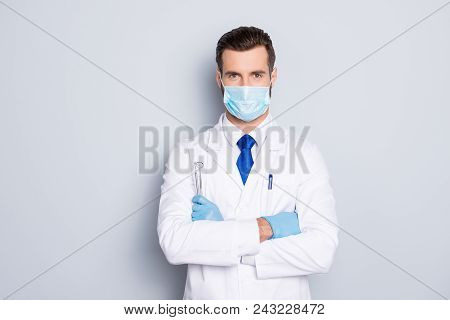 Portrait Of Attractive Handsome Dentist With Hairstyle In Protective Face Mask, White Lab Coat, Blue