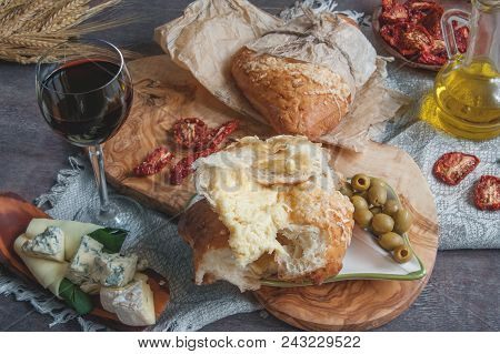 A Glass Of Dry Red Wine And Italian Focaccia Bread With Cheese And A Cheese Platter With Figs And Go