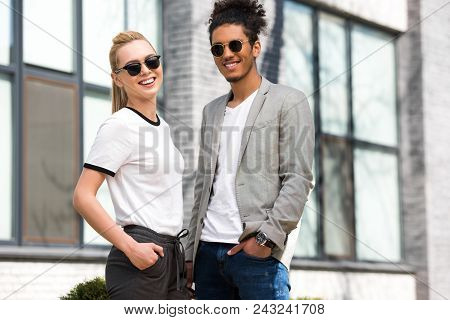 Portrait Of Beautiful Stylish Multiethnic Couple In Sunglasses Standing With Hands In Pockets And Sm