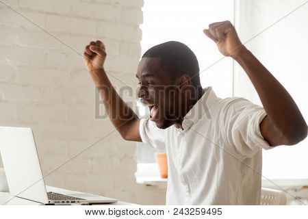 Excited Amazed Black Worker Throwing Hands Up, Screaming Celebrating Online Win, Earning Money, Reac