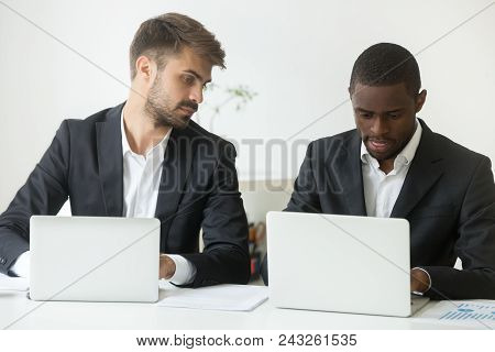 Curious Caucasian Male Businessman Looking At Screen Of African American Colleague Busy Working At L