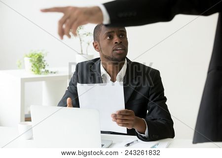 Frustrated shocked African American worker being fired, holding dismissal notice, while Caucasian employer pointing at door asking to leave. Concept of racial discrimination, employment termination poster