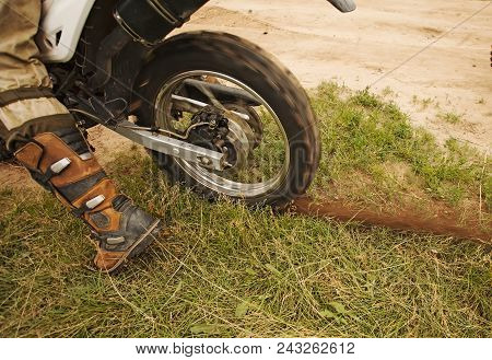 Detail View At Dirtbike Rear Wheel In Motion With Dirt Track On Grass. Man Sitting On Motocross Bike