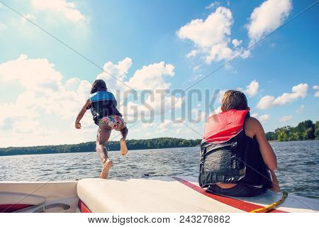 Kids jumping off a boat into the lake.