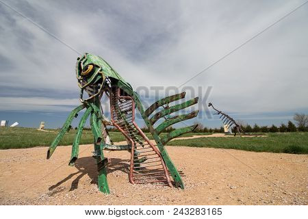 Alliance, Nebraska/usa - May 8th 2018: A Peculiar Metal Sculpture Of A Fish Leaping Out Of The Groun