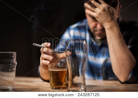 alcoholism, alcohol addiction and people concept - close up of male alcoholic drinking beer and smoking cigarette at night