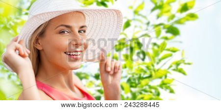 summer, fashion and people concept - portrait of beautiful smiling woman in sun hat over green natural background