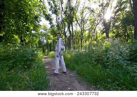A Young Guy In A Gray Sports Suit Stands Opposite The Sun Among The Trees In The Forest. Recreation