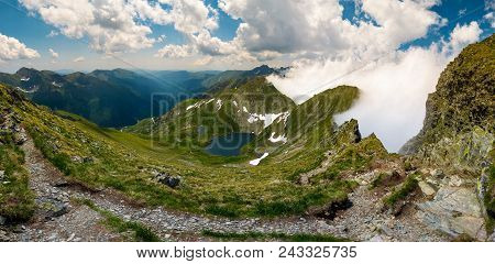 Gorgeous Landscape Of Fagaras Mountains In Summer. Clouds Rising Above The Rocky Cliffs. Lake Capra