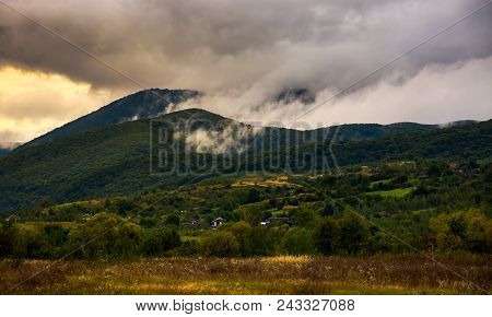 Rising Clouds In Mountainous Countryside At Menacing Sunrise. Village At The Foot Of The Mountain. R