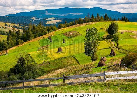 Fence In Front Of A Rural Fields On Hills. Haystack On A Grassy Slope And Mountain Ridge In The Dist