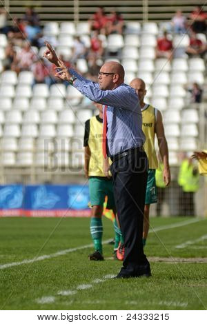 KAPOSVAR, HUNGARY - SEPTEMBER 24: Elemer Kondas Debrecen trainer (in red tie) in action at a Hungarianl Championship soccer game - Kaposvar vs Debrecen on September 24, 2011 in Kaposvar, Hungary.