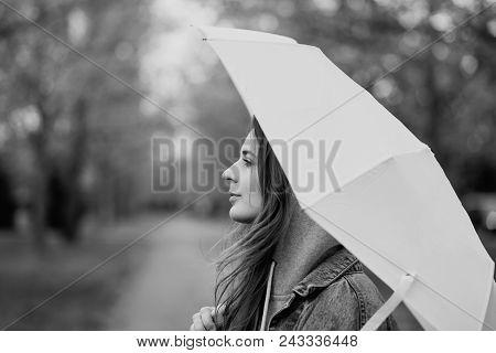Young Woman In Hood Holding An Umbrella