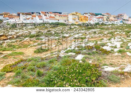 Rocky Coast At Peniche, Portugal With Small Residential Houses Clustered In The Background.
