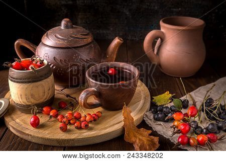 Still Life With Autumn Tea From A Dogrose And Hawthorn And A Clay Teapot On A Wooden Background.