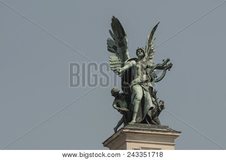 Bronze Sculpture Genius With Wings On The Roof Of The Opera House In Lvov. Blue Sky Background