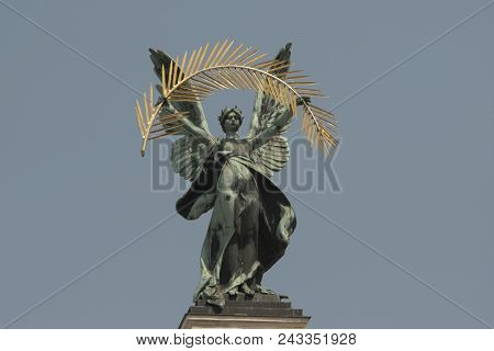 Bronze Sculpture Genius With Gold Palm Branch And Wings On The Roof Of The Opera House In Lvov. Blue