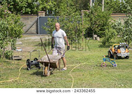 Man Pushing Wheelbarrow. Young Man Pushing A Wheelbarrow On The Farm
