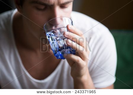 Young Man Feeling Thirsty Dehydrated Holding Glass Drinking Pure Mineral Fresh Water For Body Refres
