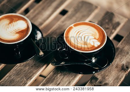 Two Cups Of Cappuccino With Latte Art In Black Cups On Wooden Table. Morning Coffee For Couple In Lo
