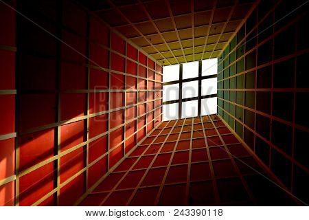 Abstract perspective of vertical lobby ceiling with skylight and strong geometry and symmetry and dramatic colors as background with space for copy. poster