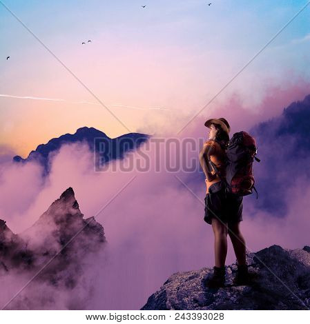 Hiker On Top Of A Mountain Cliff Admire The View.