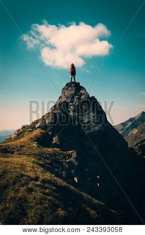 Hiker On Top Of A Mountain Hill With A Cloud Above.