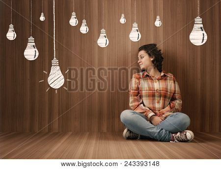 Young Woman Sits In  A Wooden Room And Looks At A Drawn Lightbulb.