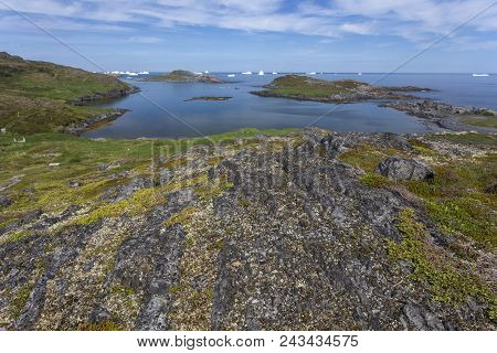 Rocky Newfoundland Coastline On Fogo Island With Distant Icebergs