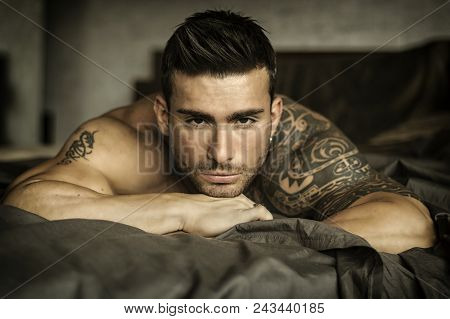 Shirtless Muscular Sexy Male Model Lying Alone On Bed In His Bedroom, Looking At Camera With A Seduc