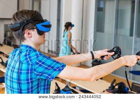 Teen Age Boy Wearing Vr Headset, Holding Controllers In Hands And Enjoying New Experience In Video G