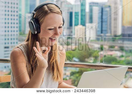 Young Woman Teaches A Foreign Language Or Learns A Foreign Language On The Internet On Her Balcony A