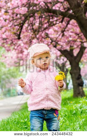 Little Charming Blonde Playing With Pleasure In The Garden In Hands Holding Flowers
